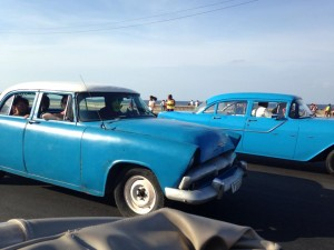 Old American cars driving along the Malacon